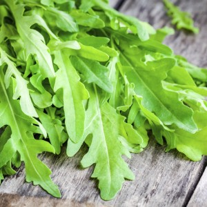bunch of fresh organic arugula on rustic table closeup