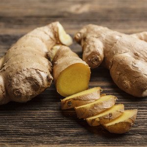 Fresh ginger, whole and sliced on rustic wooden background